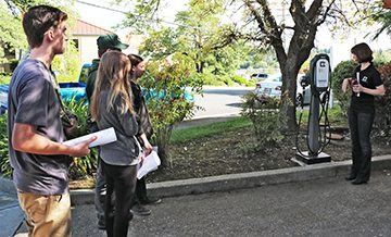 ClipperCreek's Stacey Barhydt instructs students how to use an EV charging station