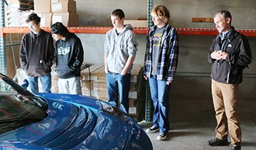 Students and Department Chair, Jonathan Schwartzc checking out the Tesla Roadster.