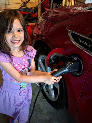 Child plugging in evse to charge an electric car